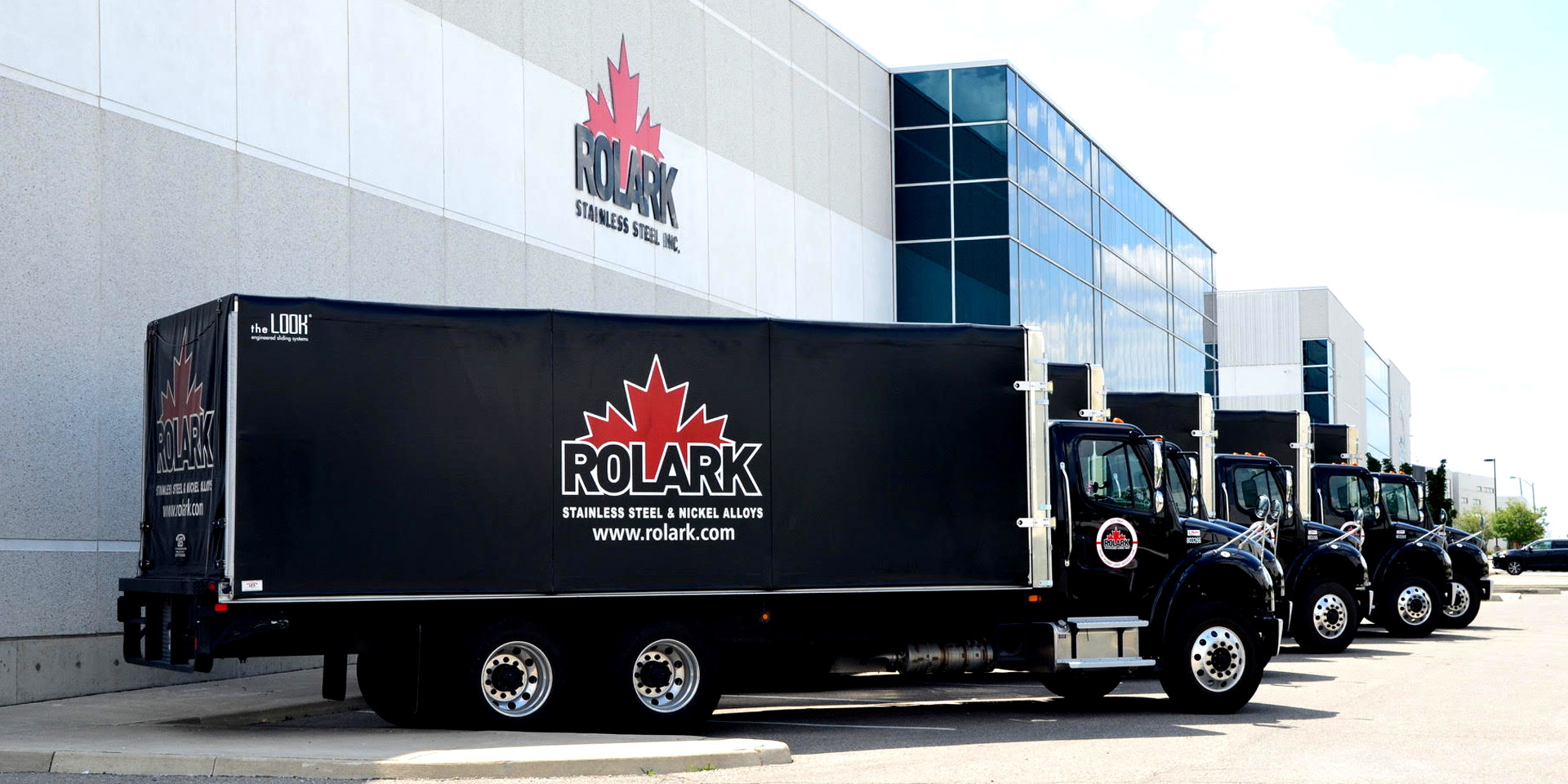 Several black Rolark trucks parked in front a a Rolark warehouse